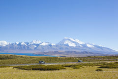 Tibet: SUVs passing by mount naimonanyi Stock Photo