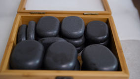 Tibet therapy - stones for stone-therapy. The doctor prepares stones for stone-therapy, pulls out of the box Royalty Free Stock Photos