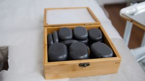 Tibet therapy - stones for stone-therapy. The doctor prepares stones for stone-therapy, pulls out of the box Stock Photography