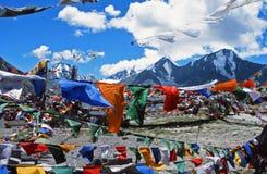 Tibetaanse die het bidden vlaggen door de wind met hoog Himalayagebergte in t worden geblazen Stock Afbeelding