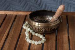 Tibetaanse zingende kom en jadeparels op een houten tribune stock foto