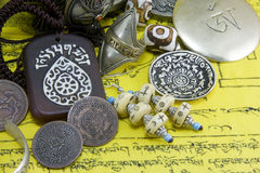 Tibetan artifacts. Various Tibetan artifacts and coins on a yellow cloth with Tibetan writings Stock Photo