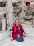 Tibetan believer meditating at the temple. A tibetan buddhist believer, meditating near Mahabodhi temple, India. He has a prayer wheel in his hand Stock Photo