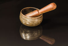 Tibetan bowl. With  black reflection and wood Royalty Free Stock Photos