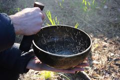 Tibetan bowl with dancing like boiling water in the sunlight in nature as a result of playing on it.  stock photos