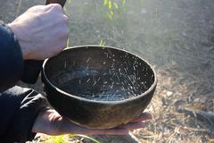 Tibetan bowl with dancing like boiling water in the sunlight in nature as a result of playing on it.  stock images