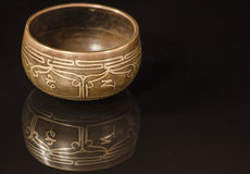 Tibetan bowl. With its reflection on black stock image
