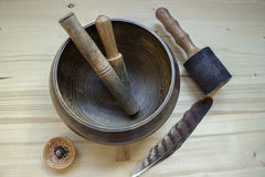 Tibetan bowl top view. On wood background. Singing bowl with wooden mallets and feather Stock Photos