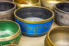 Tibetan Buddhist colored musical bowls. The inscriptions on the bowls, the mantra om mani padme hum , the literal translation of royalty free stock photos