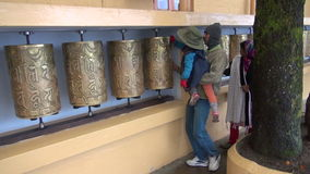 Tibetan buddhist family spin prayer wheels in Tsuglagkhang temples in Dharamsala,. Dharamshala, Himachal Pradesh – December 14: tibetan buddhist family spin stock footage