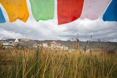 Tibetan Buddhist monastery with flag foreground. Shangri-La,Yunnan, China - October 24, 2015: Songzanlin is Tibetan Buddhist monastery. It is located in Yunnan Royalty Free Stock Photo