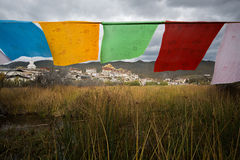 Tibetan Buddhist monastery with flag foreground. Shangri-La,Yunnan, China - October 24, 2015: Songzanlin is Tibetan Buddhist monastery. It is located in Yunnan Royalty Free Stock Images