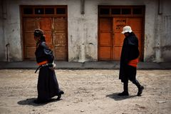 tibetan buddhist pilgrim woman and man walking in front of red wooden doors in traditional dress stock photo