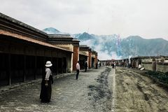 tibetan buddhist pilgrims standing in a line looking at some fireworks inside the temple walls stock images