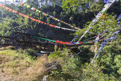 Tibetan Buddhist Prayer Flag include red, green, yellow, blue and white colors swaddle bridge and trees in Sikkim, India Stock Photos