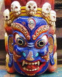 Tibetan Buddhist Wrathful Deity Mask. Colorful Tibetan Buddhist wrathful deity mask on display at a street vendor stall in Boudhanath, Kathmandu, Nepal Stock Images