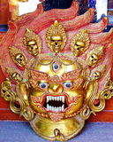Tibetan Buddhist Wrathful Deity Mask. Fierce golden image of a Tibetan Buddhist wrathful deity with fangs, skulls, and a third eye, depicted in flaming red and Stock Images