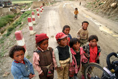 Tibetan children. Running to traveller on a bicycle, expecting a gift, remote tibetan village on a Friendship Highway, Tibet Stock Photography