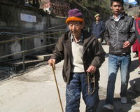 Tibetan Elder Uprising Day Dharamala India. A Tibetan elder fingering prayer beads marches down a steep street in McleodGanj Dharamsala HP India during Tibetan Stock Photos