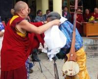 Tibetan Exiles in India Celebrate Dalai Lama's Birthday. Buddhist monk present khata prayer scarf to a man after his musical performance at Dalai Lama birthday Royalty Free Stock Photography