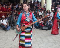Tibetan Exiles in India Celebrate Dalai Lama's Birthday. Young woman in traditional ethnic costume of Tibet performs song at Dalai Lama birthday celebrations Stock Image