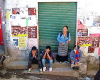 Tibetan Exiles Uprising Day Dharamsala India. Tibetan women in traditional regional costume stand beside Tibetan teenage boys in jeans and tshirts during the Royalty Free Stock Images