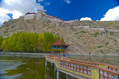 Tibetan fortress on mountain. Scenic view of old Tibetan fortress on mountain with lake in foreground Stock Images