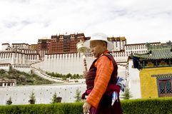 Tibetan in front of the Potala Palace. A Tibetan is wheeling his  prayer wheel Stock Image
