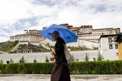 Tibetan in front of the Potala Palace. A Tibetan is wheeling his  prayer wheel Stock Photo
