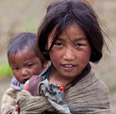 Tibetan girl. DHO TARAP - SEPTEMBER 10: Tibetan girl with baby from the village of refugees poses for the photo on September 10, 2011 in Dho Tarap, Upper Dolpo Stock Images