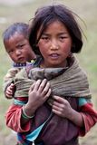 Tibetan girl with baby. DHO TARAP - SEPTEMBER 10: Tibetan girl and her brother from the village of refugees on September 10, 2011 in Dho Tarap, Upper Dolpo Stock Photo