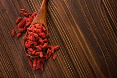 Tibetan goji berries contain many minerals. Tibetan goji berries contain many useful substances, vitamins and minerals on wooden table, view from above Stock Image