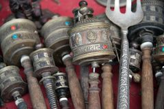 Tibetan Hand prayer wheels with wooden handles assorted styles. Tibetan Hand prayer wheels cylindrical with wooden handles assorted styles and sizes on a table Stock Photo