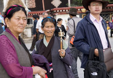 Tibetan and Hans. Together outside a temple in Lhasa ,the tibetan woman holds a pray wheel.Time:Aug.27/2010 Royalty Free Stock Photography