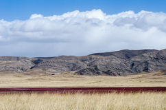Tibetan highlands and interesting red-colored lake near Daotangh Royalty Free Stock Photo