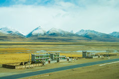 Tibetan House in countryside and Mountains Background Royalty Free Stock Photo