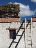 Tibetan house: a white wall, a small window, a ladder, on a flat roof lay stocks of brushwood for winter, Tibet. Royalty Free Stock Photos