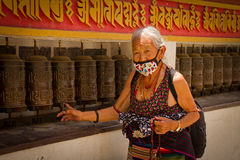 A Tibetan lady and prayer wheels, Kathmandu Nepal Stock Photography