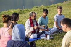 Tibetan Lama conducts classes with sunsurfers people on meditation and yoga. Pokhara, Nepal Stock Image