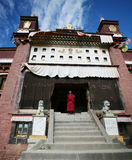 Tibetan lama at the door of monastery Stock Photos