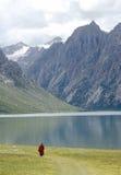 Tibetan lama pilgrim. Walking beside the lake under the mountain Royalty Free Stock Photo