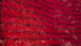 Tibetan letters on red textile. Mantra. Calligraphy. Tibetan letters on red textile. Religious writing. Prayer flags. Mantra. Buddhism. Calligraphy stock photography