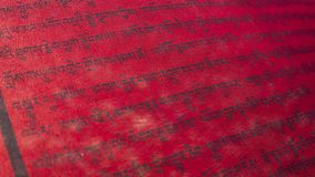 Tibetan letters on red textile. Religious writing. Prayer flags. Mantra. Buddhism stock photography