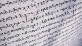 Tibetan letters on white textile. Religious writing. Prayer flags. Mantra. Buddhism. Calligraphy royalty free stock photography