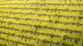 Tibetan letters on yellow textile. Religious writing. Prayer flags. Mantra. Buddhism. Calligraphy royalty free stock photography