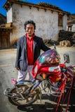 Tibetan man and his bike. Tibetan man posing for a photo with his motorbike Royalty Free Stock Image