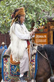 Tibetan Man on Horseback. A Tibetan man dressed in traditional fur clothing with a red panda hat sits atop his horse in the central square of Lijiang, Yunnan Royalty Free Stock Images