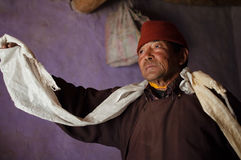 Tibetan man posing in traditional dress including white scarf - Khata. LEH, INDIA - OCTOBER 12, 2016: Tibetan man posing in traditional dress including white Stock Photography