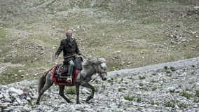 Tibetan man riding a horse. Photoed in the way of  circumambulating Mount Kailash on foot.The path around Mount Kailash is 52 km (32 mi) long.It's about 5200 Stock Images