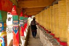 Tibetan man walking through corridor with prayer w Stock Images